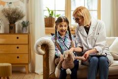 Jasnogłowy pediatra daje dziewczynie stetoskopowi próbować dalej fotografia royalty free