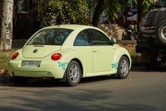Jasnozielony Volkswagen New Beetle samochód parkujący w ulicie Obraz Stock