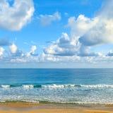 Jasny słoneczny dzień przy nadmorski Żółty piasek i błękitny ocean Zdjęcia Royalty Free