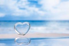 Jasny szklany serce na białym piasek plaży błyskotliwości reflec i szkle Zdjęcie Stock