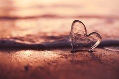 Jasny szklany serce na piasek plaży z wschodu słońca słońca światłem Zdjęcia Stock