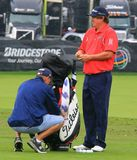Jason Dufner prior to starting his game. American professional golfer Jason Dufner prepares to start a PGA golf event as his caddie checks his bag Royalty Free Stock Images