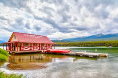 Maligne Lake in Jasper National Park in Alberta Canada. JASPER, CANADA - JUL 10, 2018: Colorful canoes lie on the Maligne Lake Boat House dock in Jasper National Royalty Free Stock Image