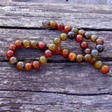 Jasper necklace. Colourful jasper beads thread on a wooden background Royalty Free Stock Images