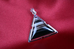 Jasper Pendant. An antique Triangular Silver Pendant with Jasper stone kept on a crimson cloth Stock Photography