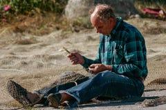 Jastarnia, Polonia, il 17 agosto 2007: Il pescatore anziano ripara la rete Immagini Stock Libere da Diritti