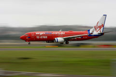Jato azul de Boeing 737 do Virgin no movimento. Imagem de Stock Royalty Free