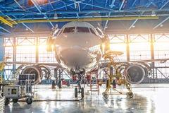 Jato civil do avião na manutenção do reparo da verificação do motor e da fuselagem no hangar do aeroporto Luz brilhante na porta fotos de stock