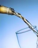 Jato da cerveja da garrafa no vidro no fundo azul Fotos de Stock Royalty Free