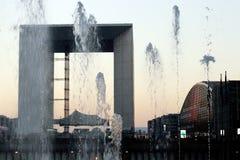 Jato de água grandioso do arche da defesa do La no distrito financeiro de Paris no por do sol france do inverno Fotografia de Stock Royalty Free