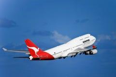 Jato de Qantas Boeing 747 no vôo em um céu azul Imagens de Stock