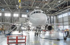 Jato dos aviões comerciais na manutenção do reparo da verificação do motor e da fuselagem no hangar do aeroporto imagens de stock