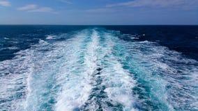 Jato espumoso branco atrás da embarcação em um fundo do mar azul Foto de Stock Royalty Free