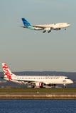 Jato regional ERJ-190 de Austrália Embraer do Virgin em Sydney Airport com uma aterrissagem de Garuda Airways Airbus A330 atrás Imagens de Stock
