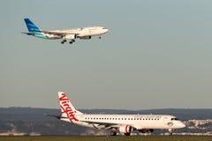 Jato regional ERJ-190 de Austrália Embraer do Virgin em Sydney Airport com uma aterrissagem de Garuda Airways Airbus A330 atrás Imagem de Stock Royalty Free