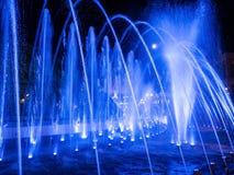 Jatos de água coloridos na fonte na noite com Lua cheia foto de stock royalty free