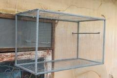 Jaula de pájaros vacía en la pared Imagenes de archivo