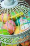 Jaula decorativa con los huevos de Pascua pintados Imagen de archivo libre de regalías