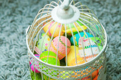 Jaula decorativa con los huevos de Pascua pintados Imagenes de archivo