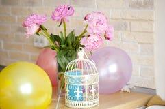 Jaula decorativa para los pájaros, ramo de peonías, globos Foto de archivo