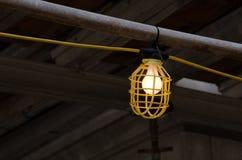 Jaula plástica del guardia de la lámpara con la bombilla encendida en el emplazamiento de la obra Imagenes de archivo
