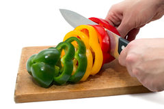 Jaune coupé, rouge et poivrons verts et un couteau de cuisine sur un conseil en bois Photos libres de droits