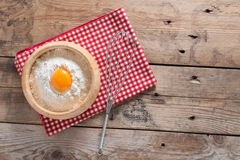 Jaune d'oeuf dans la farine et le fouet pour battre sur la table en bois principal vi Photographie stock