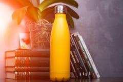 Jaune de bouteille thermo de couleur au-dessus du fond des livres et de la fleur verte Avec l'effet de lumière du soleil photos stock