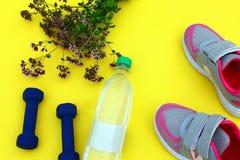 Jaune de couverture avec des haltères, une bouteille de l'eau et des espadrilles sur l'herbe verte fraîche Photographie stock libre de droits