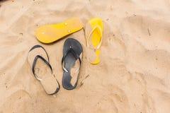 Jaune de noir de pantoufles de pieds de sable de plage Photographie stock