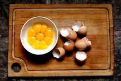 Jaunes d'oeuf dans des coquilles d'une cuvette blanche et d'oeufs sur un fond en bois Image stock
