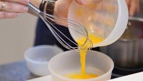 Jaunes d'oeuf fouettés avec du sucre dans un bol en verre Les jaunes d'oeuf battus dans une cuvette avec battent Jaune d'oeuf bat Images stock
