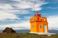 Jaunissez avec le phare orange sur l'océan bleu et le fond nuageux de ciel bleu, Islande Images libres de droits