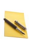 Jaunissez le bloc-notes avec le stylo-plume Photos stock