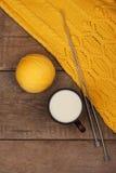 Jaunissez le chandail tricoté et une tasse de lait sur la table en bois Photographie stock libre de droits