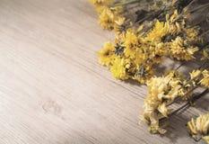 Jaunissez les fleurs sèches sur le fond en bois rustique de planches Photos libres de droits