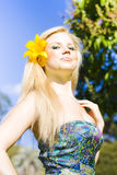 Jaunty Beauty With Flower. Jaunty beautiful young woman wearing a bright yellow flower in her hair with her head held high, low angle portrait Stock Photos