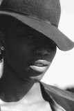 Jaunty elegant attractive African woman. Jaunty elegant attractive young African woman wearing her trendy hat at a rakish angle over one eye looking at the Royalty Free Stock Image