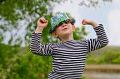Jaunty macho little boy in a colorful trendy hat. Jaunty macho little boy colorful trendy hat  mischievous grin raising his arms in air as he shows off in a Stock Photo