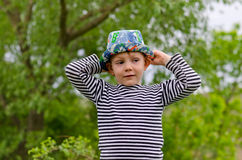 Jaunty macho little boy in a colorful trendy hat. With mischievous grin raising his arms air as he shows summer park Royalty Free Stock Images