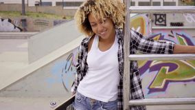 Jaunty sexy young woman carrying a skateboard stock footage