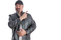 Jaunty trendy man pointing to blank copyspace. Jaunty trendy middle-aged man with a goatee wearing a grey leather jacket and cap pointing to blank copyspace for Stock Images