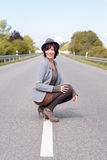 Jaunty trendy young woman crouching on a road Stock Photography