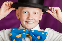 Jaunty young boy in a bow-tie and top hat. Jaunty young boy in a large out sized blue polka dot bow-tie and top hat holding his hands to the brim as he grins Stock Image