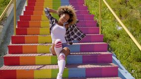 Jaunty young woman sitting on rainbow steps stock video