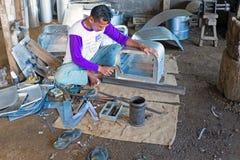 JAVA,印度尼西亚- 2016年12月21日:做厨房utens的工作者 免版税库存图片