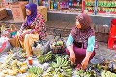 JAVA,印度尼西亚- 2016年12月18日:卖在市场上的妇女香蕉在印度尼西亚 免版税库存照片