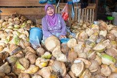 JAVA,印度尼西亚- 2016年12月18日:卖椰子的销售妇女 免版税库存图片