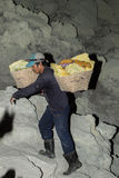 JAVA, INDONESIA - AUGUST, 9, 2016 - Miners carrying sulfur from Ijen Volcano Blue flames at night stock image