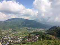 Java, Indonesia. A view from the mountain road on hills with green fields and the village in the valley stock photography